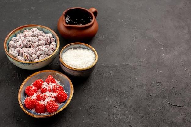 Вид спереди разные конфеты с шоколадным сиропом на темном фоне цветного конфетного чая и печенья