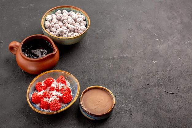 Вид спереди разные конфеты с шоколадным сиропом на темно-сером фоне цвета конфеты, чай, бисквит
