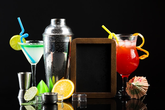 Front view of different cocktails with shaker and blackboard