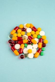 Vista frontale diverse pillole colorate sulla superficie blu virus laboratorio salute covid-ospedale scienza droga pandemia colori