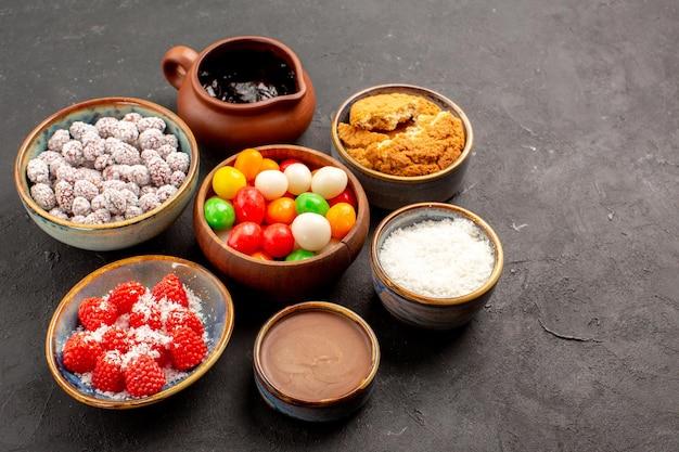 Вид спереди разные красочные конфеты с конфитюрами на темном фоне цветного конфетного чая и печенья