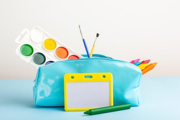 青い机の上の青いペンボックス内のさまざまなカラフルな鉛筆と絵の具の正面図