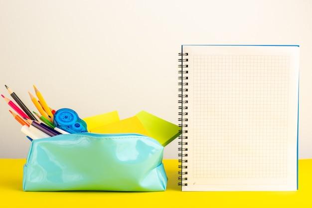 黄色の机の上のコピーブックと青いペンボックス内のさまざまなカラフルな鉛筆の正面図