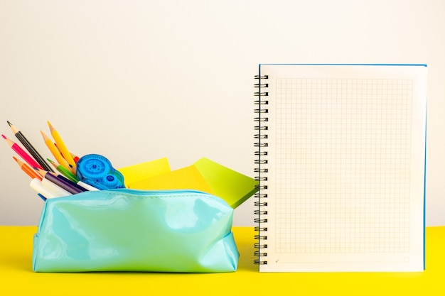 Matite colorate differenti di vista frontale all'interno della scatola blu della penna con il quaderno sullo scrittorio giallo