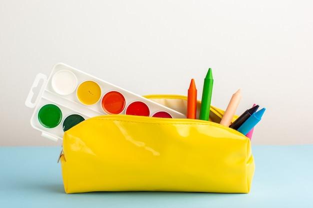 Matite colorate differenti vista frontale all'interno della scatola della penna gialla sul pavimento blu