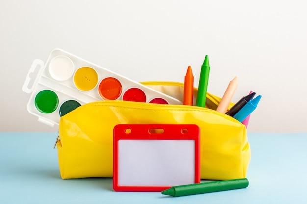 青い床の黄色いペンボックス内のさまざまなカラフルな鉛筆の正面図