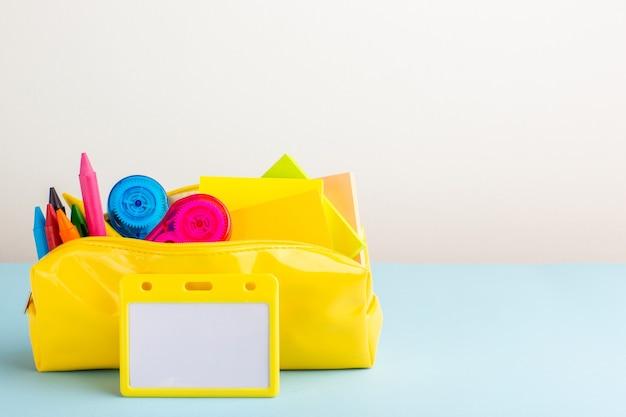 青い机の上の黄色いペンボックス内のさまざまなカラフルな鉛筆の正面図