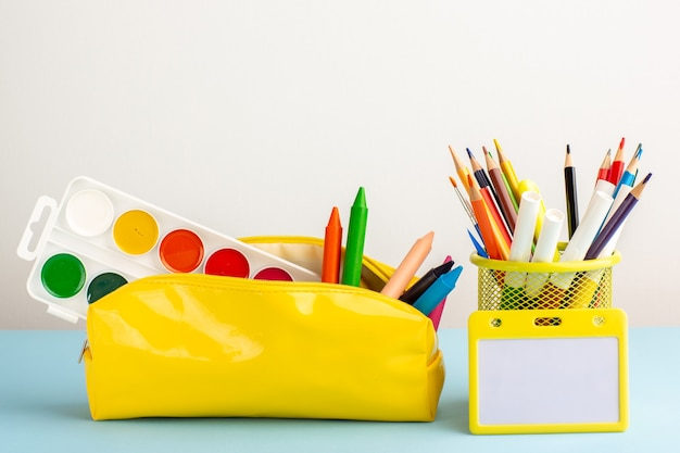 Diverse matite colorate di vista frontale all'interno della scatola della penna gialla con il quaderno sulla scrivania blu