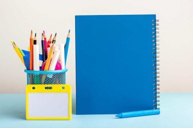 青い机の上の青いコピーブックとさまざまなカラフルな鉛筆の正面図