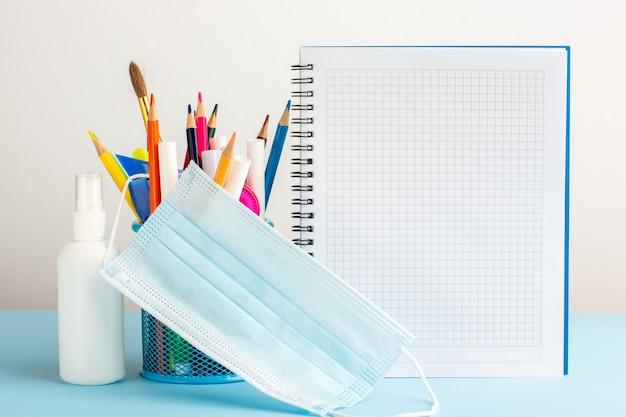 コピーブックと青い机の上のスプレーでさまざまなカラフルな鉛筆の正面図