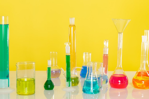 Front view of different colorful solutions inside flasks on the table