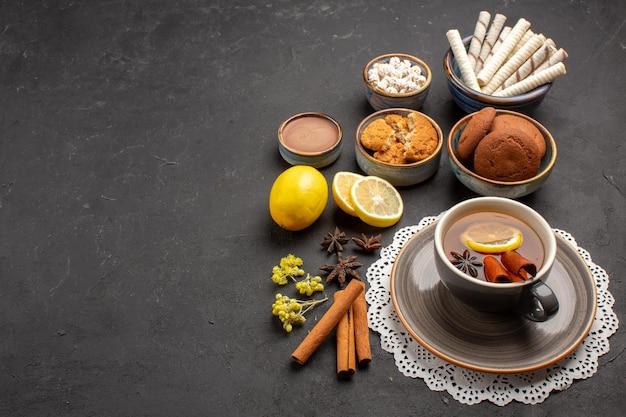 Vista frontale diversi biscotti con una tazza di tè e fette di limone su sfondo scuro biscotto dolce biscotto agli agrumi zucchero di frutta