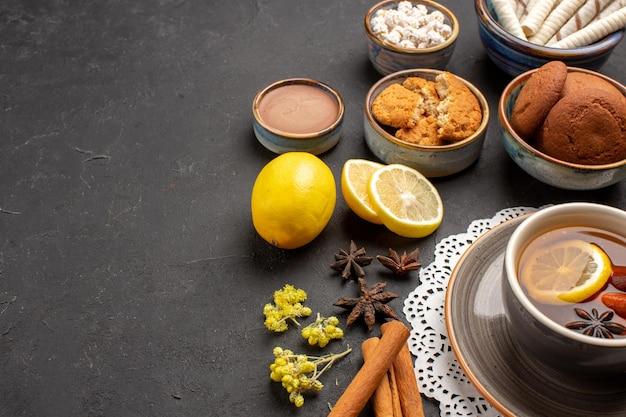 Vista frontale diversi biscotti con una tazza di tè e fette di limone su sfondo scuro biscotti dolci biscotti agli agrumi zucchero di frutta