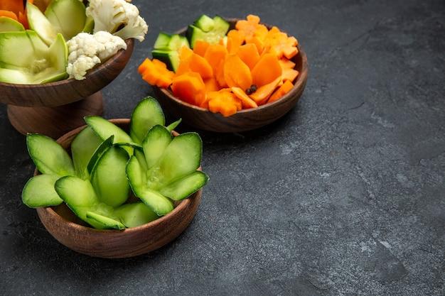 ダークグレーのスペースにある鉢の中のさまざまなデザインの野菜の正面図