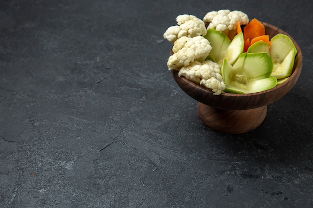 ダークグレーの机の上のさまざまなデザインの野菜の正面図