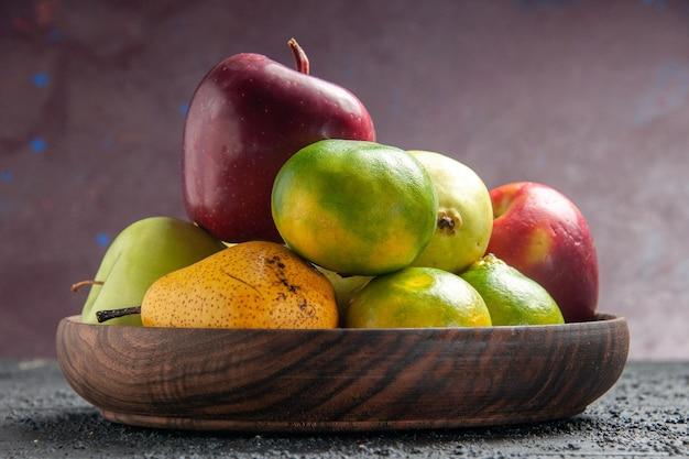 Vista frontale diversi frutti freschi mele pere e mandarini all'interno del piatto sulla scrivania blu scuro composizione colore frutta fresca matura