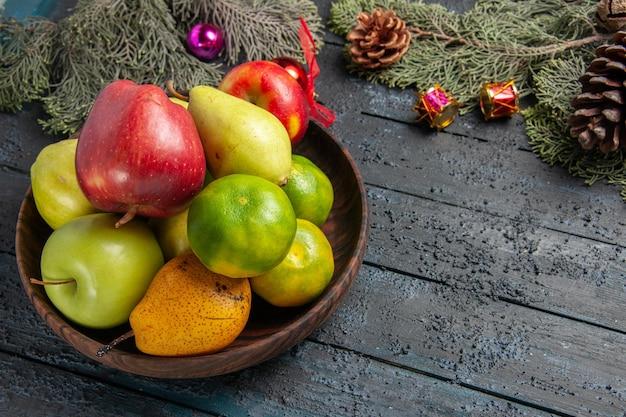 짙은 파란색 책상 과일 색상 구성에 있는 갈색 접시 안에 있는 다양한 신선한 과일을 전면에서 볼 수 있습니다. 무료 사진