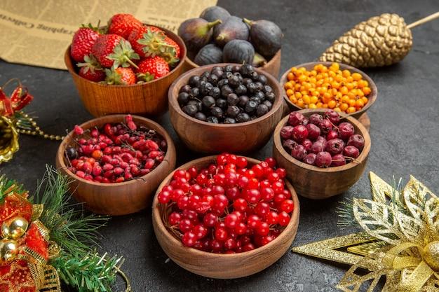Вид спереди разных свежих фруктов внутри тарелок на темном фоне, фото спелых многих цветов фруктов