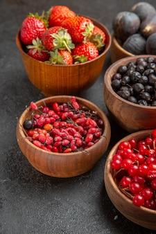 Вид спереди разные свежие фрукты внутри тарелок на темном столе, цветная фотография фруктов, много спелого сока
