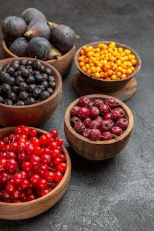Вид спереди разные свежие фрукты внутри тарелок на темном полу цветная фотография фруктов много спелых соков