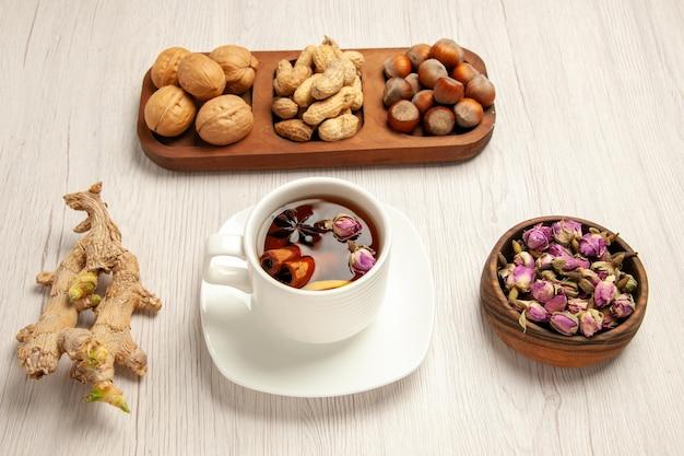 흰색 책상 너트 스낵 많은 식물에 차를 곁들인 다양한 신선한 견과류 땅콩 헤이즐넛과 호두의 전면 전망