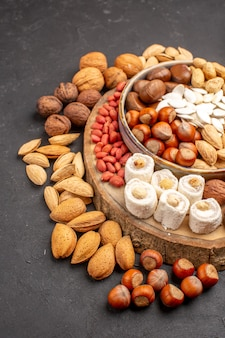 Front view of different fresh nuts with confitures on dark surface