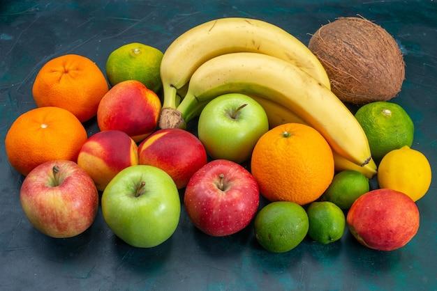 Вид спереди разные фруктовые композиции бананы мандарины яблоки на темно-синем столе фрукты свежие спелые спелые цвета витамин