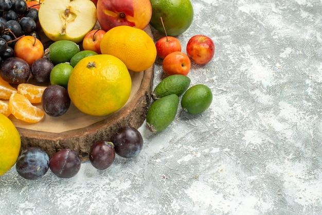 白いスペースに新鮮な果物を丸ごとスライスした正面図のさまざまな果物組成