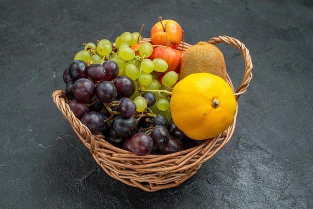 正面図さまざまな果物の組成新鮮で熟した濃い灰色の背景のバスケットの内側まろやかな新鮮な果物の健康熟した
