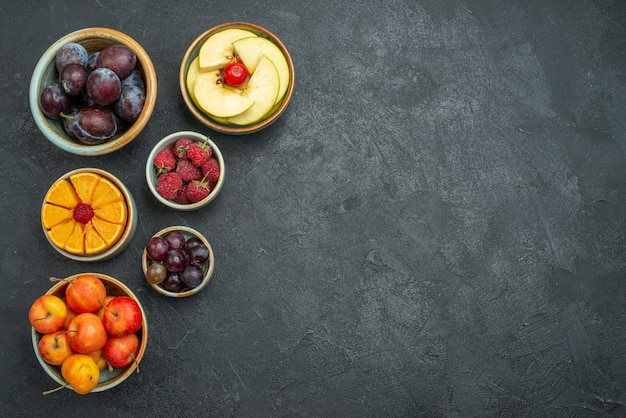 Front view different fruits composition fresh fruits on dark background health fresh ripe fruit mellow