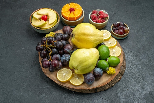 Front view different fruits composition fresh and ripe on dark-grey background ripe mellow fruits health plant color