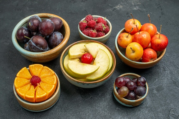 Front view different fruits composition fresh and sliced fruits on dark background fresh ripe fruits mellow health