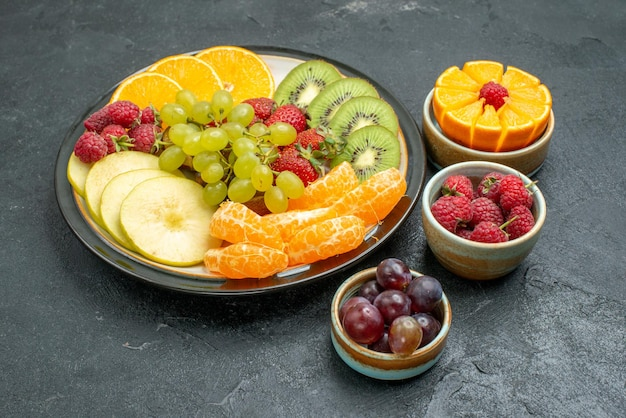Vista frontale composizione di diversi frutti frutta fresca e affettata su sfondo scuro frutta fresca e matura dolce