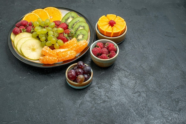 Front view different fruits composition fresh and sliced fruits on dark background health fresh ripe fruits mellow