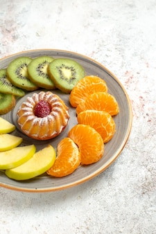 Front view different fruits composition fresh and sliced fruits with little cake on a white background mellow ripe fruits health