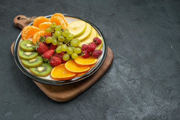 Front view different fruits composition fresh sliced and ripe on the grey background mellow fresh fruits health ripe