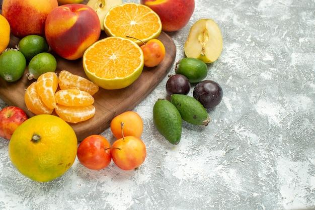 白いスペースにスライスされたさまざまな果物の正面図と新鮮な果物全体