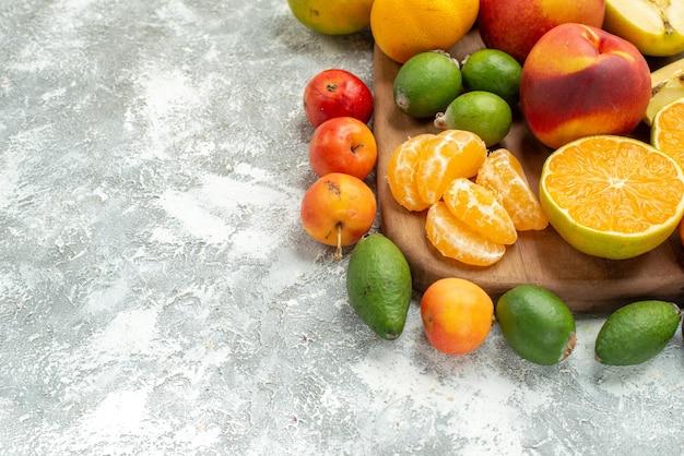 Вид спереди различные нарезанные фрукты и целые свежие фрукты на белом пространстве