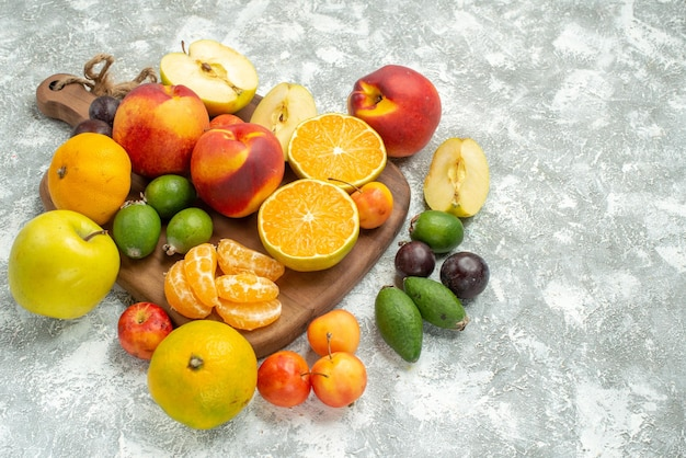 Front view different fruits composition sliced and whole fresh fruits on a white space