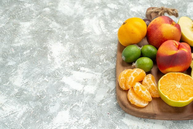 Vista frontale composizione di frutta diversa affettata e frutta fresca intera su spazio bianco