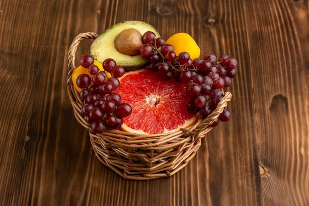 Front view different fruits inside basket on brown wooden desk