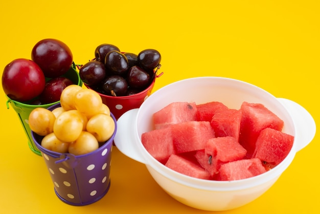 A front view different fruits inside baskets with sliced watermelon on yellow, color fruit composition