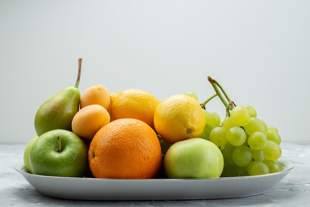 A front view different fruits such as lemons pears apples grapes and oranges on the white desk inside plate fruit color vitamine summer fresh