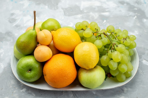A front view different fruits such as lemons pears apples grapes and oranges on the white desk inside plate fruit color vitamine summer
