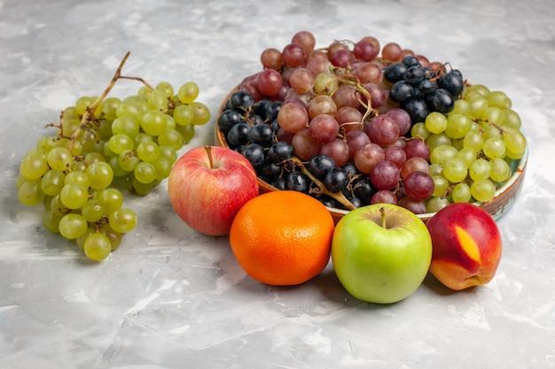 Вид спереди разные сорта винограда, свежие кислые фрукты на светлом белом столе, фрукты, свежий спелый сок, лето