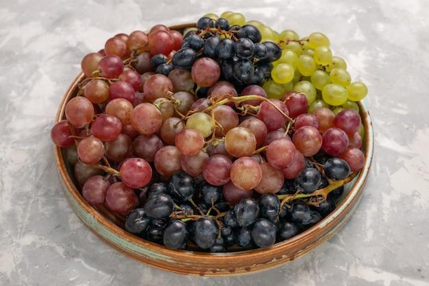 Вид спереди разные сорта винограда сочные спелые кислые фрукты на светлом белом столе фруктовый свежий мягкий сок вино