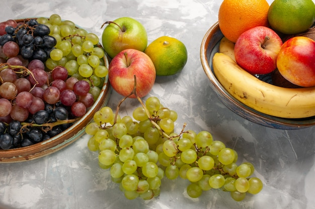 Вид спереди разные сорта винограда с другими фруктами на белой поверхности фруктов свежий мягкий сок летом