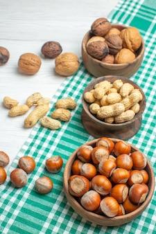 Вид спереди разные орехи, арахис, фундук и грецкие орехи на белой поверхности