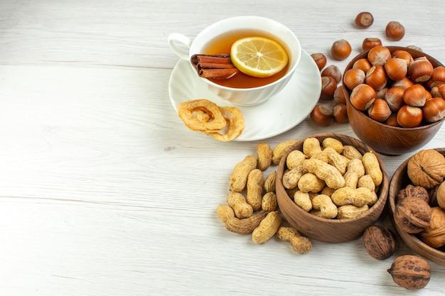 Вид спереди разные орехи, арахис, фундук и грецкие орехи с чашкой чая на белой поверхности