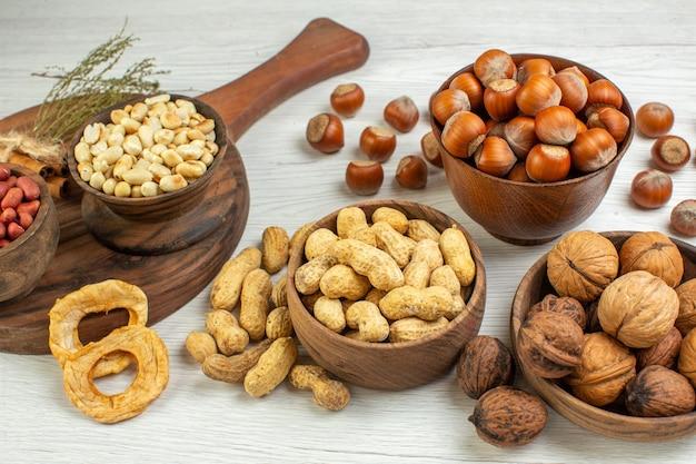 Vista frontale diverse noci arachidi nocciole e noci su superficie bianca